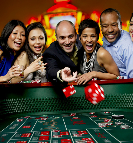 Excited friends gambling at craps table in casino