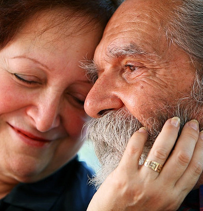 Affectionate old couple with the wife holding on lovingly to the husband's face. Focus on the husband's eyes. Concept: Elderly love.