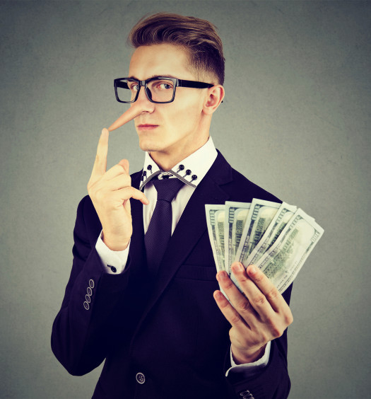 Financial fraud concept. Liar young business man in suit and glasses with dollar cash